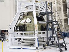 Technicians lower a special fixture<br /> around an Orion spacecraft inside the<br /> high bay of the Operations &amp; Checkout<br /> Building at NASA&#39;s Kennedy Space Center<br /> in Florida.<br /> Photo credit: NASA/Tim Jacobs